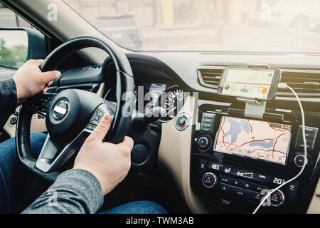 Closeup of man hands holding steering wheel. Person sitting in car using smartphone and build-in satellite navigator GPS. Modern gadgets in real life - Stock Photo