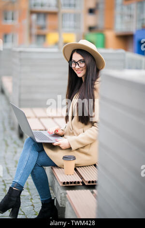 Portrait of woman wearing coat working on laptop while sitting on bench in city street - Stock Photo