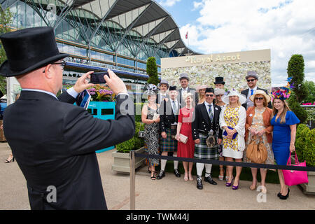 Ascot, Berkshire, UK. 21st June, 2019. A man in a top hat takes a photo of a group of racegoers on day four at Royal Ascot, Ascot Racecourse. Credit: Maureen McLean/Alamy Live News - Stock Photo