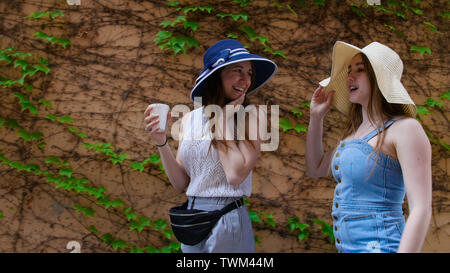 Two young keen women walking on the street and talking - Stock Photo