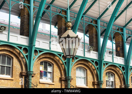 Detail of a lamp hanging from the steel roof of Covent Garden Market in London United Kingdom . - Stock Photo