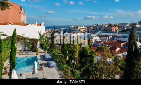 Lisbon, Portugal cityscape overlooking Baixa downtown area. Luxurious empty swimming on left with balcony view - Stock Photo