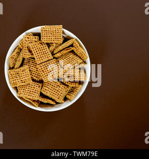 Bowl of Wholegrain Shreddies Breakfast Cereals Against a Brown Background With No People - Stock Photo
