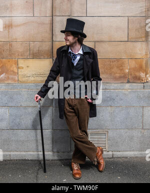 Glasgow, Scotland, UK. 21st June, 2019. UK Weather. A young man called Ian dressed as a Victorian Gentleman with a top hat, a great coat and waistcoat, and carrying a silver tipped walking stick, enjoys a sunny day in Glasgow. Credit: Skully/Alamy Live News - Stock Photo