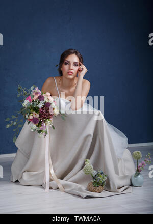 Dreaming young bride with beautiful hair and makeup, with a bouquet of flowers, sitting on a chair in the Studio at the blue wall - Stock Photo