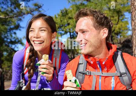 Couple eating muesli bar hiking. Happy people enjoying granola cereal bars living healthy active lifestyle in mountain nature. Woman and man hiker sitting laughing during hike. - Stock Photo