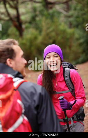 Couple having fun laughing hiking in forest. Multicultural woman and man hikers on hike in woods wearing backpacks outdoors in nature. - Stock Photo