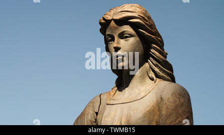 Angel statue in warm sunlight and blue sky. - Stock Photo