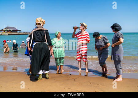 Broadstairs Dickens Festival. Five senior men and women dressed in Victorian bathing costumes, standing on the sea shore at Viking Bay beach. Man standing in the middle drinking beer from a bottle, others watching him. - Stock Photo
