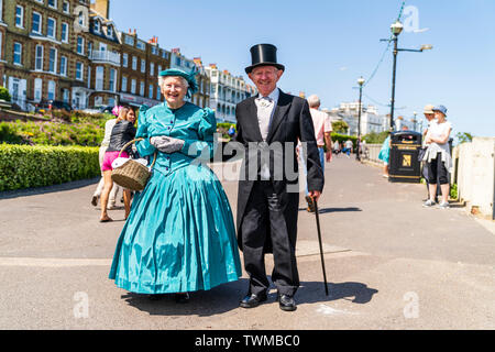 Broadstairs Dickens Festival. Elderly, senior couple, dressed in upper class Victorian costume, she in a dress and matching hat, he in black suit with cane and top hat. Strolling along the seafront promenade in bright sunshine. Eye contact, smiling. - Stock Photo