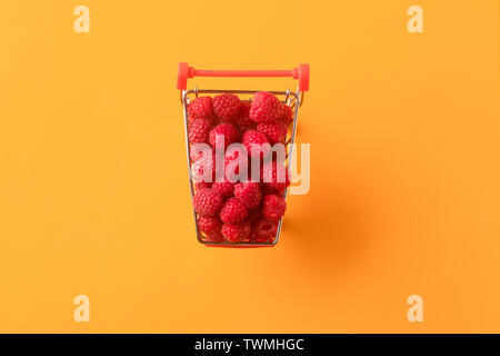 ripe raspberries in shopping cart on orange background, concept buying sweet berries, flat lay.