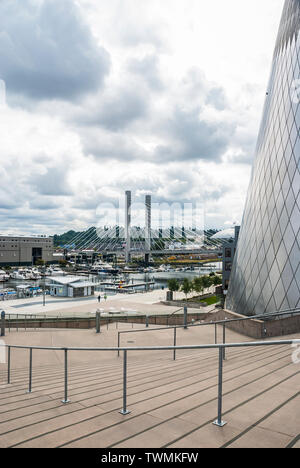 Exterior of the Museum of Glass in Tacoma, Washington, showing the marina, the E. 21st Street Bridge, and a partial view of the Tacoma Dome. - Stock Photo