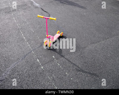 Colour image of a pink and yellow child's scooter on a road, shot from above and in front, with the late afternoon sun casting long shadows - Stock Photo