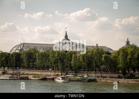 Paris, France - July 06, 2018: A view from a distance of the Grand Palace and the embankment of the Seine on the opposite bank against the blue cloudy - Stock Photo