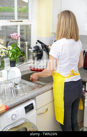 Young Woman in yellow apron washing dishes and cleaning kitchen. Housekeeper washes pate in sink. Domestic life - Stock Photo