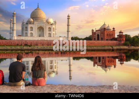 Taj Mahal sunset view from Mehtab Bagh on the banks of river Yamuna with a tourist couple enjoying a romantic moment.