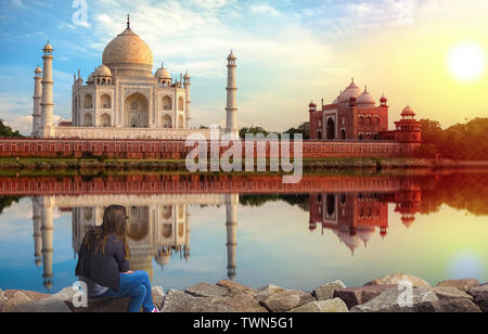 Taj Mahal Agra sunset view with young female tourist enjoying the view from Mehtab Bagh on the banks of river Yamuna