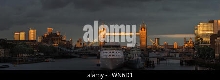 London, England. June 21, 2019. The sun illuminates Tower Bridge as Silver Wind cruise ship moors next to HMS Belfast on the River Thames in London. - Stock Photo