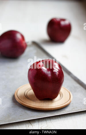 three red Apples on grey background - Stock Photo