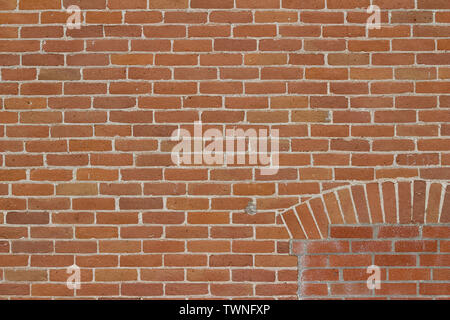 Old 19th Century weathered orange red brick wall background in traditional running bond brickwork pattern - Stock Photo