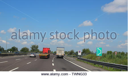 Cars and trucks on motorway with four lanes near Milan (Italy) - Stock Photo