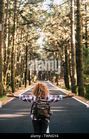 Alternative travel concept with curly hipster woman viewed from back open his arms and feel the freedom of the outdoors nature standing in the middle