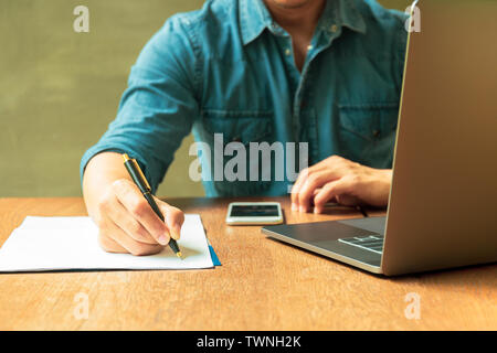 Man writing document on paperwork with laptop and cell phone on wooden desk. - Stock Photo