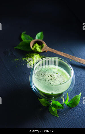 Matcha tea with foam in a double wall glass with a wooden spoon with matcha powder on a dark background with copy space - Stock Photo