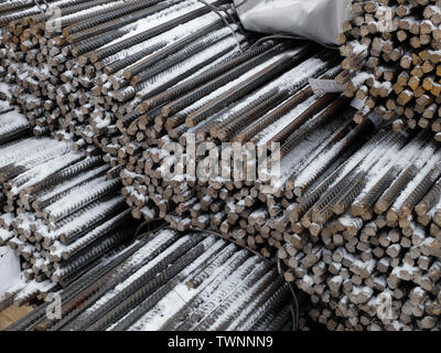 Steel snow covered reinforcement bars at the outdoor warehouse, industrial background, building armature. - Stock Photo