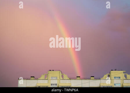 Rainbow over the roof of a multi-storey city house in the evening pink sunset sky after the rain, summer fantastically beautiful magical landscape. - Stock Photo