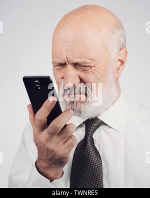 Senior man using apps on the smartphone, he is having difficulties and vision problems - Stock Photo