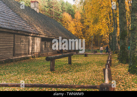Visitors of the Ethnographic Open-Air Museum of Latvia walking towards Latvian traditional wooden tavern. - Stock Photo