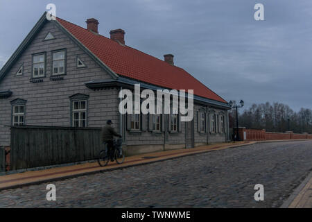 A man riding on a bike near renovated old house at the end of Kuldīga red brick bridge. - Stock Photo