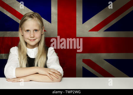 Happy child student sitting in classroom against the UK flag background. Learn English language concept - Stock Photo