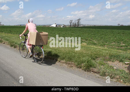 Amish woman riding a bike on a country road in Lancaster County, PA, USA - Stock Photo