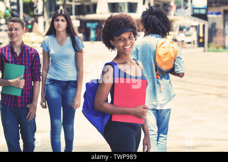 Young african american female student waiting for bus outdoors in city in summer - Stock Photo