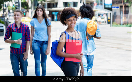 Laughing african american female student waiting for bus outdoors in city in summer - Stock Photo