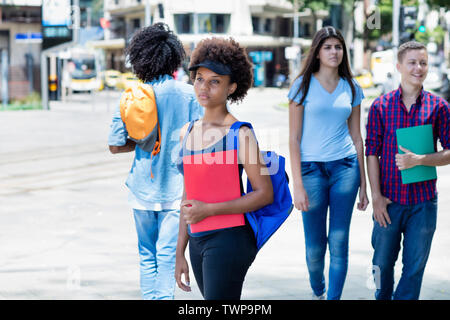 African american female student waiting for bus outdoors in city in summer - Stock Photo