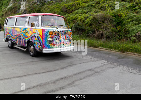 Painted Volkswagen van in vivid colors driving in the street in the city of San Francisco - Stock Photo