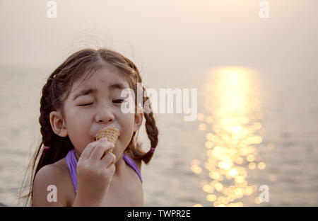 cute asian girl eating ice cream to reduce tempurature with sunset on the beach - Stock Photo