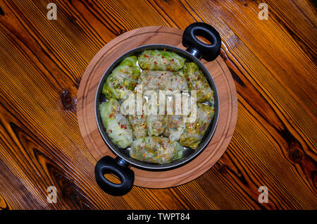 Cabbage Rolls, Dolma. Stuffed cabbage leaves with minced meat, rice, vegetables, herbs in plate. Isolated on rustic wooden table, cutting board - Stock Photo