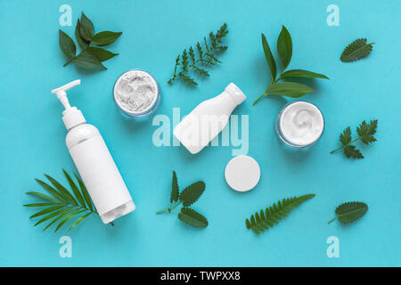 Natural cosmetics and green leaves on blue background, top view, flat lay. Natural organic skincare, bio research and healthy lifestyle concept. - Stock Photo