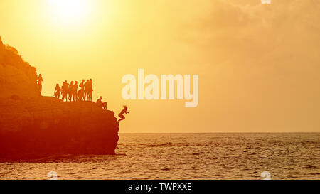 Summer fun with best friends cliff jumping into ocean at sunset - Stock Photo