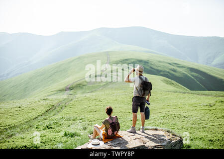 Couple enjoying beautiful landscape views, resting on the rock while traveling in the mountains during the summer time - Stock Photo