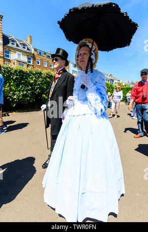 Yearly Broadstairs Dickens Festival. The main parade on seafront promenade, with People dressed up In Victorian costume as Dickensian characters. Couple strolling along seafront. Mature woman in white dress with black parasol and man in black flock coat, and top hat. - Stock Photo