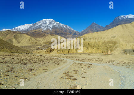 Dirt track leading to the village of Ghemi, partly visible in the distance. Upper Mustang region, Nepal. - Stock Photo