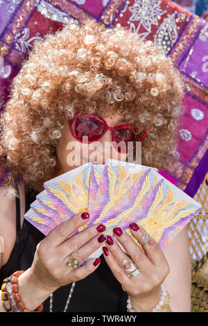 A female clairvoyant reads tarot cards on her stand at the Africa Oye music festival in Liverpool sefton park - Stock Photo