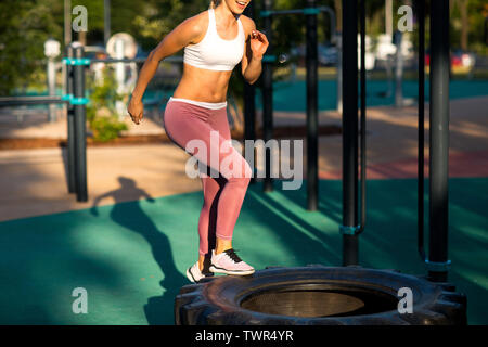 Young woman is training on the outdoor playground. Crossfit and fitness workout outdoors. - Stock Photo