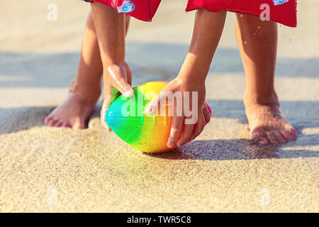 Baby feet walking on sand beach grabbing rugby ball – playful toddler wearing inflatable armbands hand holding ball from water in summer vacation - Stock Photo