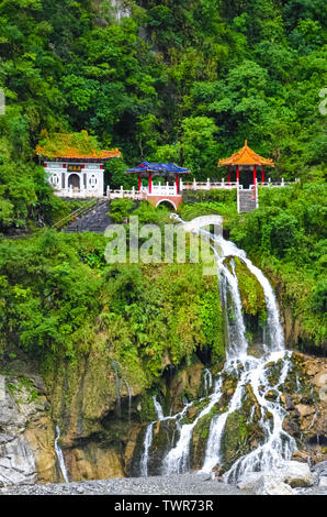 Changchun temple, landmark and a memorial shrine complex in Taroko National Park in Taiwan. The monument is located right above the beautiful waterfall streams. Tropical forest around. Rocks. - Stock Photo